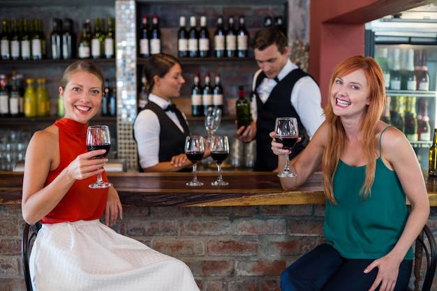Портрет счастливой женщины, держащей бокал красного вина за барной стойкой