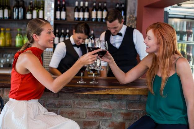 Счастливая женщина поджаривания бокал красного вина на барной стойке