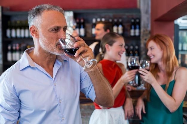 Мужчина пьет красное вино, а двое друзей поджаривают бокалы