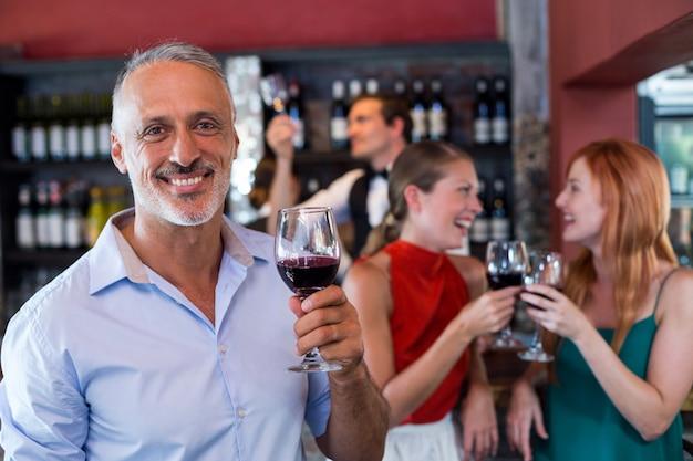 Портрет улыбающегося человека, держащего стакан красного вина