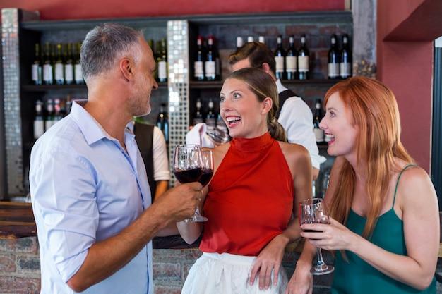 Друзья тостов с бокалом красного вина в баре
