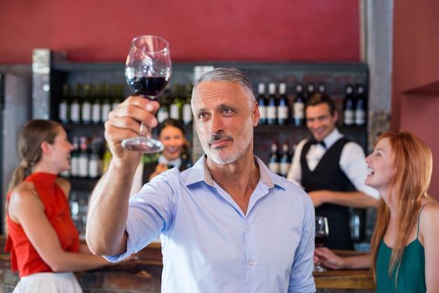 Человек тостов с бокалом красного вина в баре