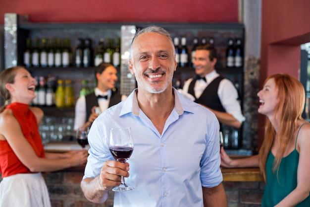 Портрет человека, держащего бокал перед барной стойкой