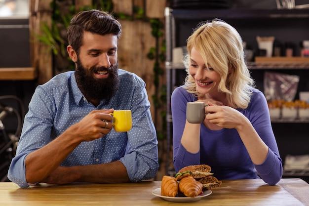 Пара ест круассан и пьет кофе