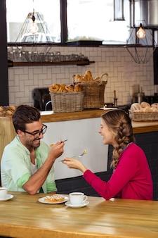 Улыбающиеся пары едят торт