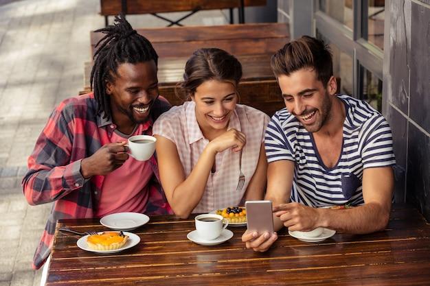 Друзья вместе используют смартфон