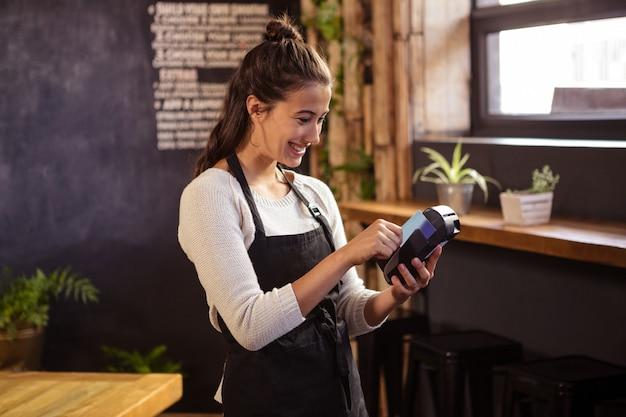 Улыбающаяся официантка с помощью считывателя банковских карт