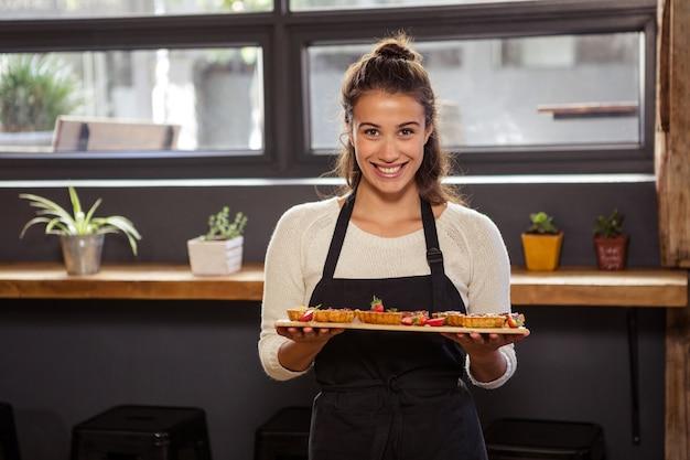 Официантка держит поднос с тарталетками