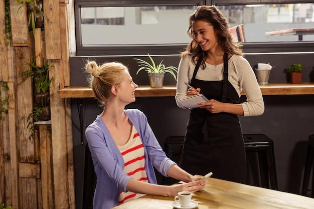 Официантка принимает заказ женщины