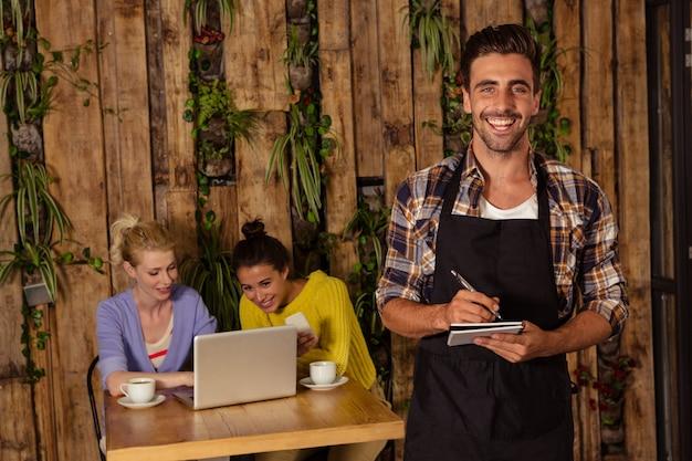 Официант принимает заказ перед двумя друзьями