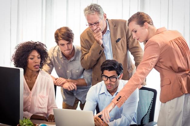ノートパソコンを議論するビジネス人々