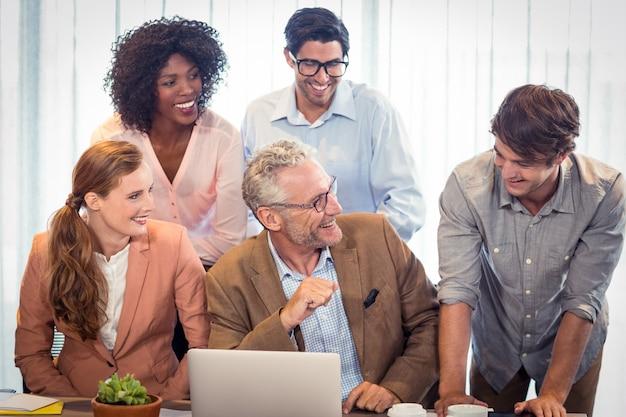 Деловые люди обсуждают за ноутбуком
