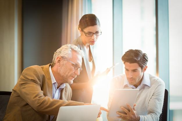 デジタルタブレットを議論するビジネス人々