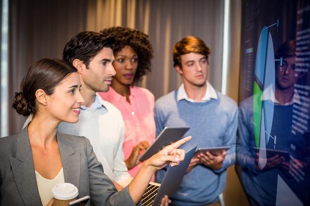 会議室のグラフを見ているビジネス人々