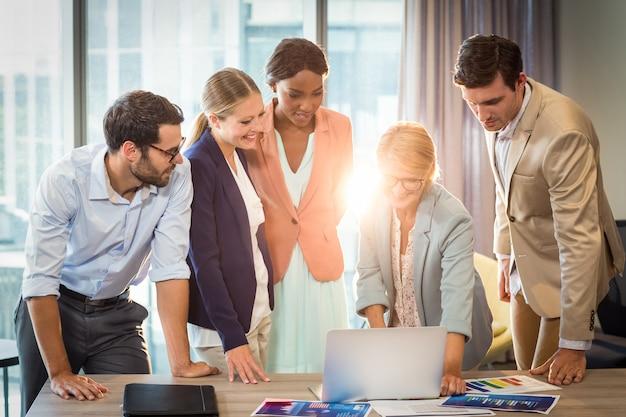 ラップトップを使用して対話するビジネス人々のグループ
