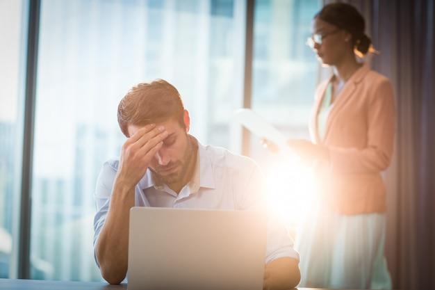 頭の上の手で机の上に座っている欲求不満の実業家