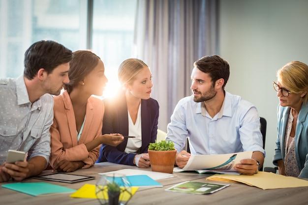 デスクで議論するビジネス人々のグループ