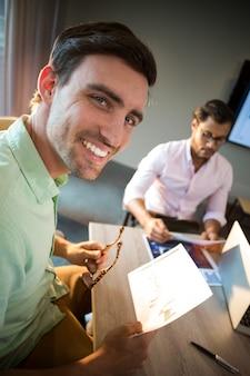 彼の同僚が文書を読んでいる間カメラに笑顔の男