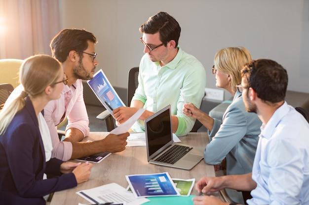 会議中にグラフを議論するビジネス人々