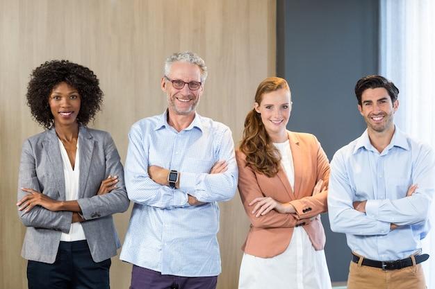 Портрет улыбающихся деловых людей, стоящих вместе со скрещенными руками