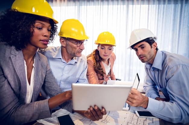 Архитекторы обсуждают над цифровым планшетом в офисе