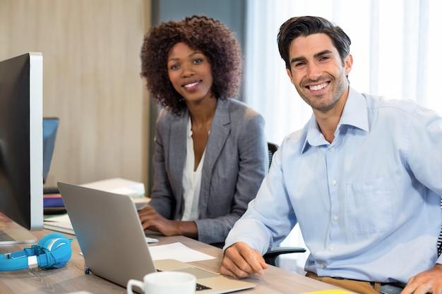 Улыбающиеся люди бизнеса, сидя в офисе