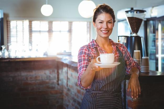 一杯のコーヒーを保持しているウェイトレス