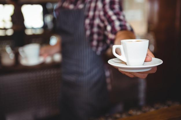 Официант, сдающий кофе