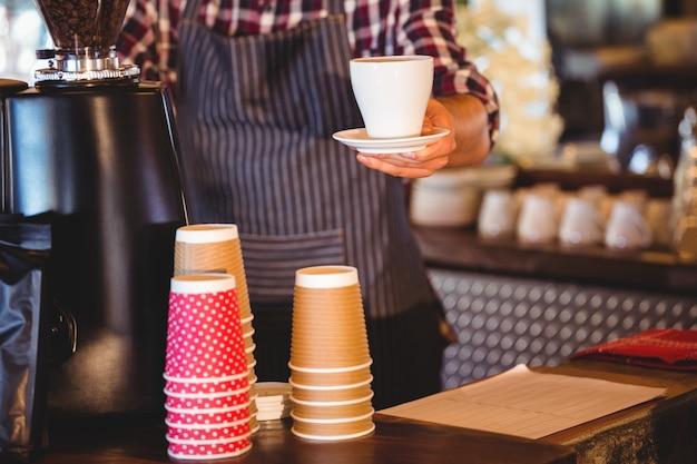 コーヒーを引き渡すウェイター