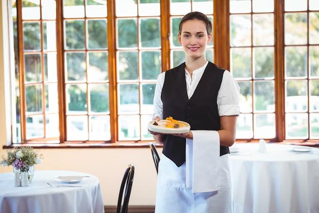 Официантка держит тарелку с пирожными