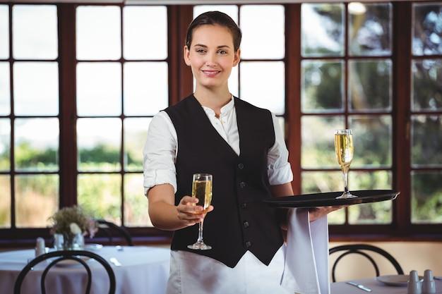 シャンパンを提供している笑顔のウェイトレスの肖像画