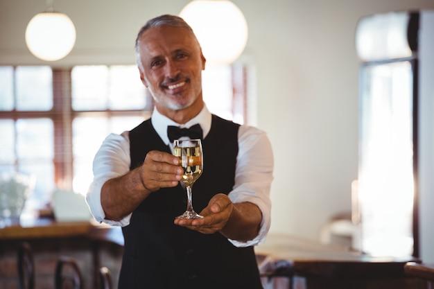 バーカウンターでグラスワインを提供するバーテンダーの笑顔