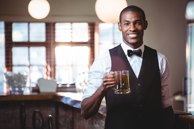 バーカウンターでビールのグラスを提供する笑顔のバーテンダー