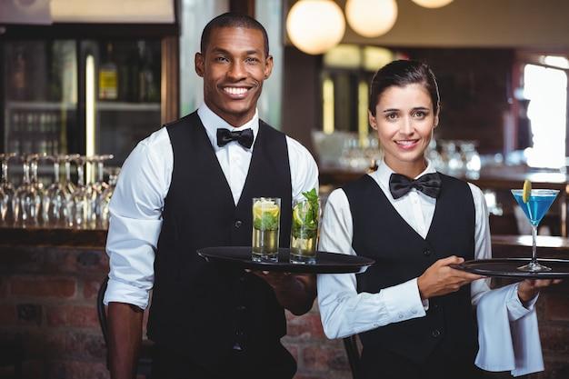 Официант и официантка, держа поднос с бокалом коктейля
