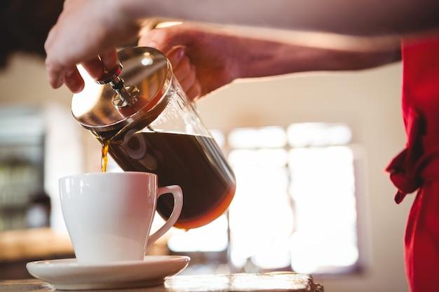 Средняя часть официанта наливает чашку кофе