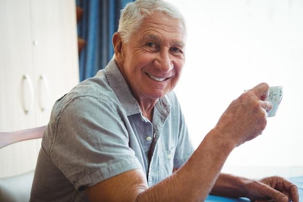 Отставной улыбающийся мужчина держит чашку чая