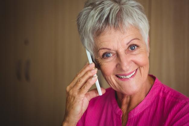 電話をかける笑顔の引退した女性の肖像画