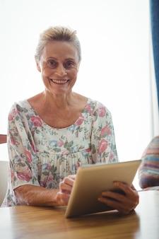 デジタルタブレットを使用してカメラを見て年配の女性