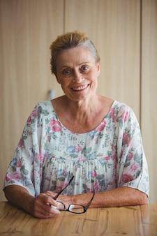 テーブルに座っている眼鏡を保持している年配の女性の笑顔