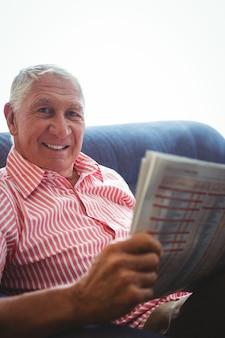 新聞を押しながらカメラ目線のソファーに座っている年配の男性