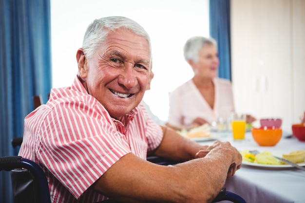 Старший мужчина, улыбаясь в камеру