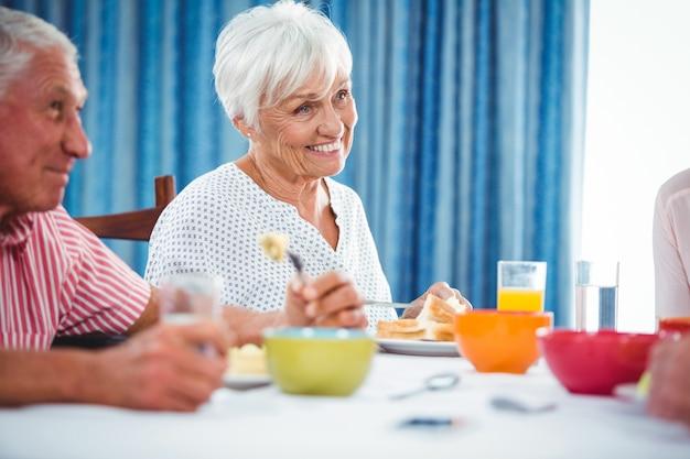 Старшая усмехаясь женщина во время завтрака