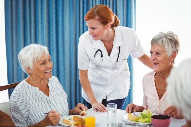 Улыбающаяся медсестра, глядя на старшего человека во время завтрака