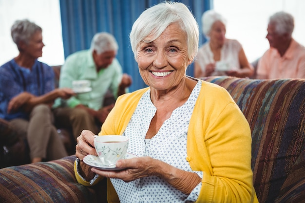 一杯のコーヒーを保持している笑顔の年配の女性