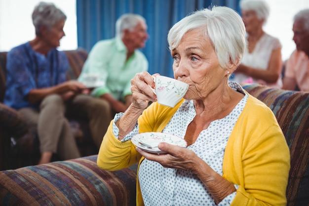 年配の女性が一杯のコーヒーを飲む