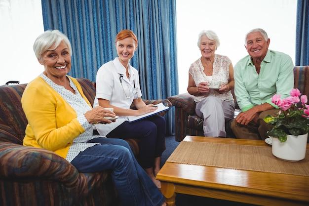 Пожилые люди и медсестра смотрят в камеру