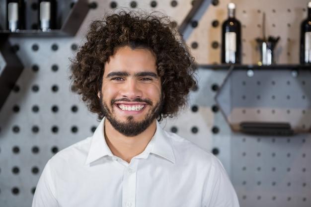 バーカウンターに立っている笑顔のバーテンダー
