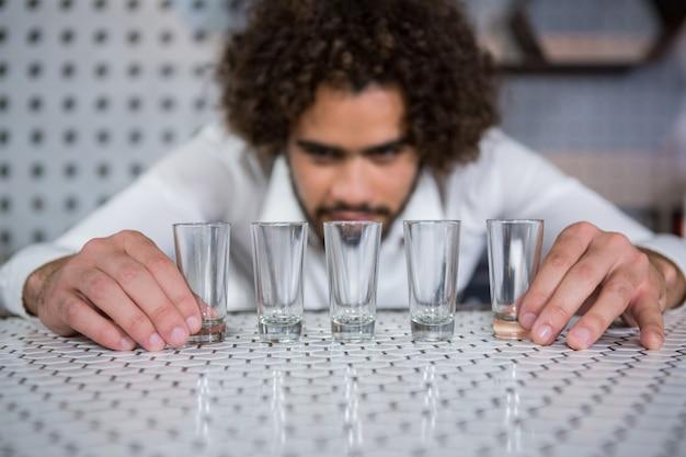 バーカウンターにショットグラスを置くバーテンダー