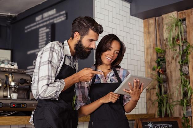 Улыбающиеся официант и официантка, взаимодействующие при использовании цифрового планшета