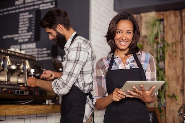 Официантка с помощью цифрового планшета в то время как официант готовит кофе в фоновом режиме